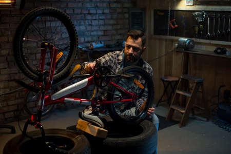 Shot of a man working in a bicycle repair shop alone