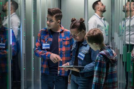 Medium long shot of an IT technician showing around children in a server park