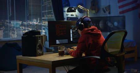 Medium shot of a programmer coding on his computer at night Stock Photo