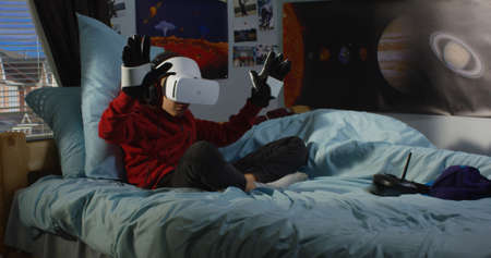 Full shot of a boy wearing VR headset and controlling his toy robot with exoskeleton gloves