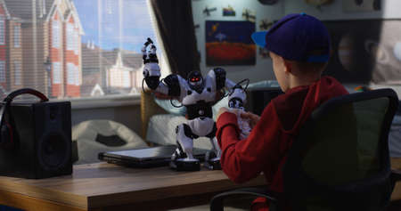 Medium shot of a boy controlling his toy robot with exoskeleton gloves 写真素材