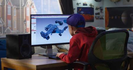 Medium shot of a boy using a computer to design a futuristic airplane at home