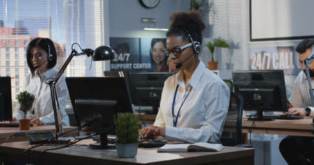 Medium shot of young woman working at her desk in a call center