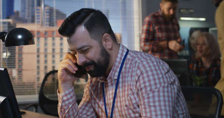 Medium shot of man talking to phone at an office