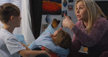 Plano medio de una madre hablando con hermanos discutiendo Foto de archivo