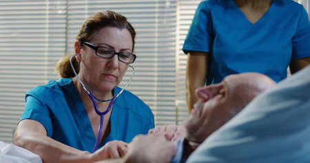 Medium shot of a female doctor talking to male patient who is lying in hospital bed