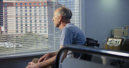Elderly sad male patient in a wheelchair at the hospital looks out the window then turn to camera and look at the camera