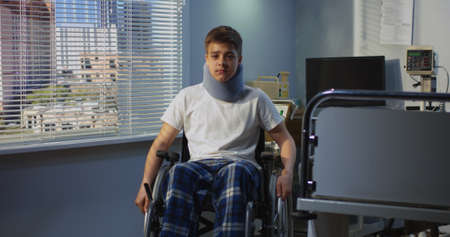 Medium shot of teenager boy sitting in wheelchair in hospital and looking at camera 스톡 콘텐츠