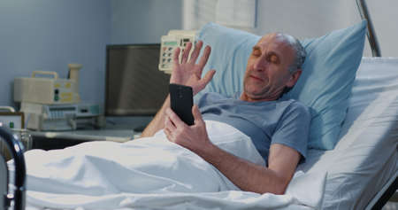 Medium shot of senior adult patient using video call in hospital room