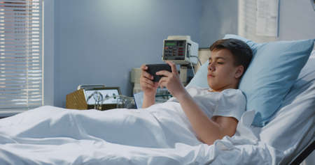 Medium shot of teenager patient lying in hospital bed and playing with game