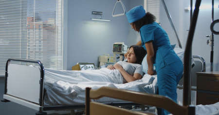 Medium shot of doctor and male nurse lifting patient to bed in hospital Stock Photo
