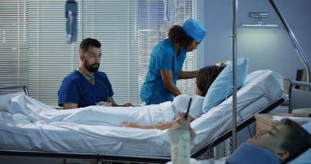 Medium shot of teenager patients and doctors in hospital room 写真素材 - 121126875