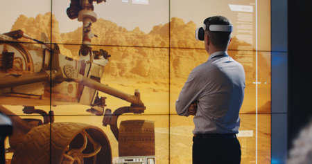 Medium long shot of Mars mission leader using VR headset and technicians working in the background