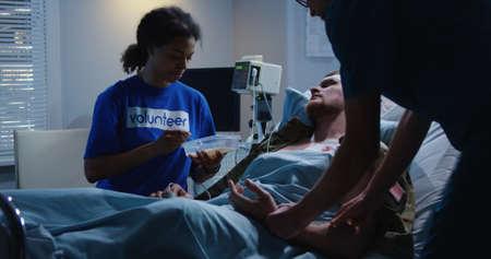 Medium shot of volunteer feeding injured soldier in hospital bed Imagens