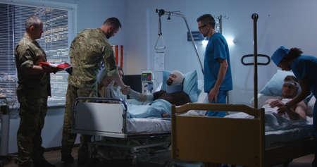 Un plan moyen d'un soldat blessé reçoit un insigne d'honneur dans une chambre d'hôpital