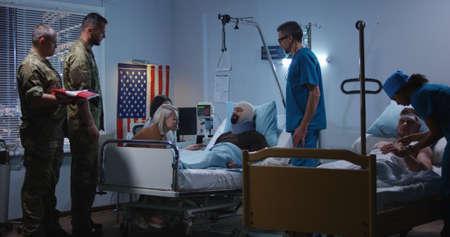 Un plan moyen d'un soldat blessé reçoit un insigne d'honneur dans une chambre d'hôpital Banque d'images