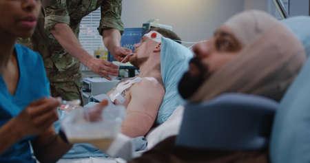 Medium shot of a nurse feeding injured soldiers in hospital bed