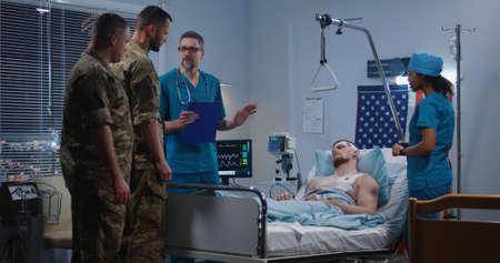Plan moyen d'un médecin montrant une radiographie aux visiteurs pendant qu'un soldat blessé est allongé dans son lit