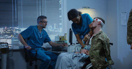 Medium shot of soldier sitting in wheelchair while doctors checking medical device