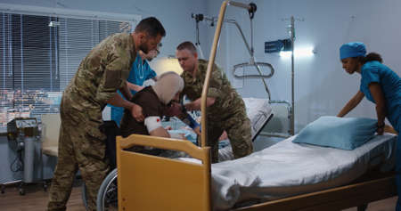 Medium shot of soldiers helping their fellow getting to bed in hospital among doctor and nurse Stock Photo