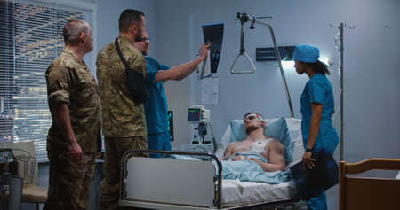 Medium shot of doctor showing x ray to visitors while wounded soldier lying in bed