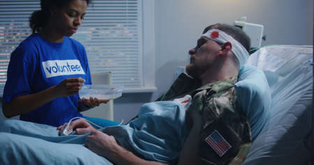 Medium shot of volunteer feeding injured soldier in hospital bed 写真素材