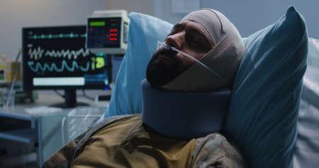 Medium shot of injured soldier lying in hospital bed 写真素材