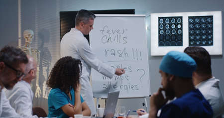 Medium shot of a doctor explaining diagnosis to his colleagues while writing symptoms on a whiteboard