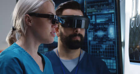 Medium shot of a male and a female doctor discussing results of a brain scan while wearing VR headsets 写真素材