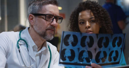 Medium close-up of a male and a female doctor analyzing MRI scan results