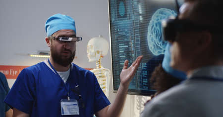 Medium shot of a VR headset wearing male doctor explaining to his colleagues while moving his hands