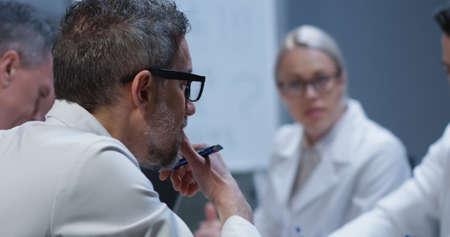 Medium close-up of doctors discussing bone injury while analyzing x-ray image