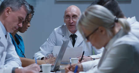 Medium shot of doctors talking and taking notes during a meeting 写真素材