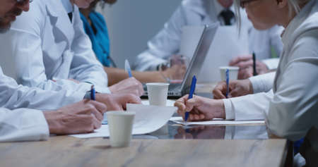 Medium shot of doctors analyzing cervical spine x-ray during a meeting 写真素材
