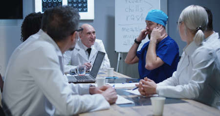 Medium shot of doctor making his colleagues laugh with telling a story