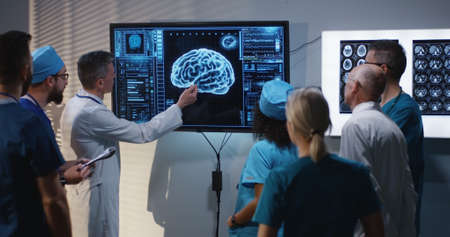 Medium shot of a doctors discussing brain damage diagnosis at a digital screen with a 3D image of a brain