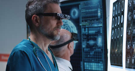 Medium close-up of male doctors examining results of a brain scan with VR headset