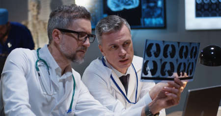 Medium close-up of two male doctors analyzing MRI scan results