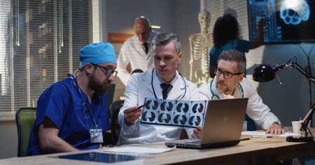 Medium close-up of three male doctors analyzing MRI scan results 写真素材