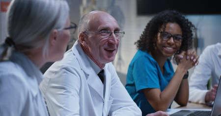 Medium shot of doctors having a cheerful conversation during a meeting 写真素材