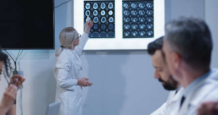 Medium shot of doctors watching their young female colleague explaining diagnosis with brain scan 写真素材