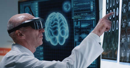 Medium close-up of a male doctor examining image of a brain scan with VR headset