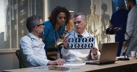 Medium shot of a female and two male doctors analyzing MRI scan results 写真素材