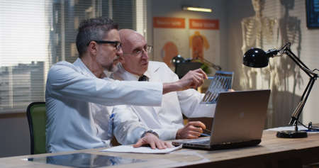 Medium shot of two male doctors analyzing MRI scan results