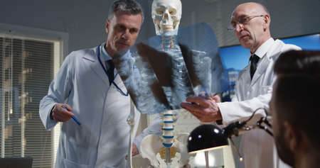 Medium shot of a male doctor explaining diagnosis to his colleagues with a cervical spine x-ray and a skeleton