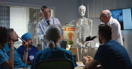 Medium shot of doctors explaining diagnosis to their colleagues with a cervical spine x-ray and a skeleton 写真素材