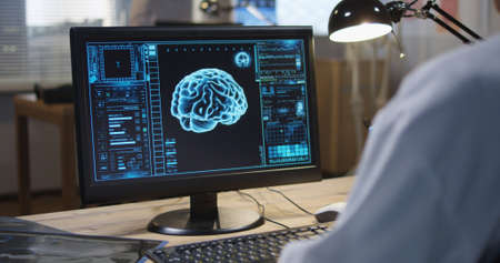 Medium shot of doctor sitting at monitor and analyzing x ray and brain scan