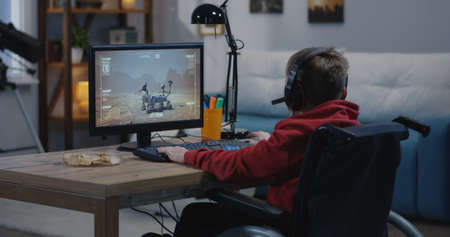 Medium shot of a boy watching the movement of a Mars rover on his computer at home