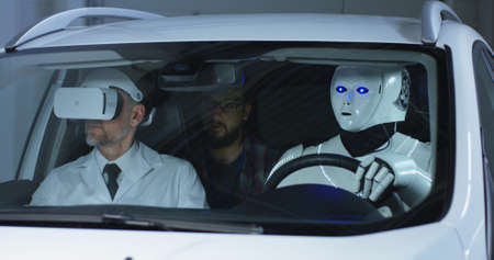 Medium shot of two male scientists testing a car driving humanoid robot Stock Photo