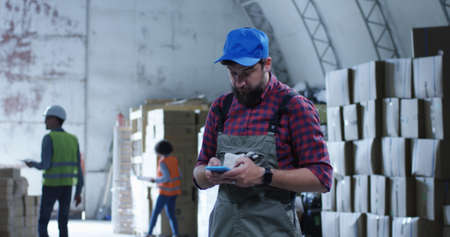 Medium shot of worker using phone in a warehouse